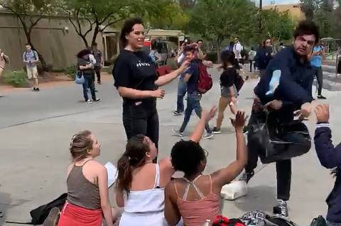 An unidentified male throws a granola bar at students working at a Turning Point USA booth at U ...