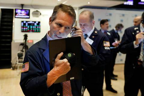 Trader Robert Charmak, left, works on the floor May 1, 2019, of the New York Stock Exchange. (A ...