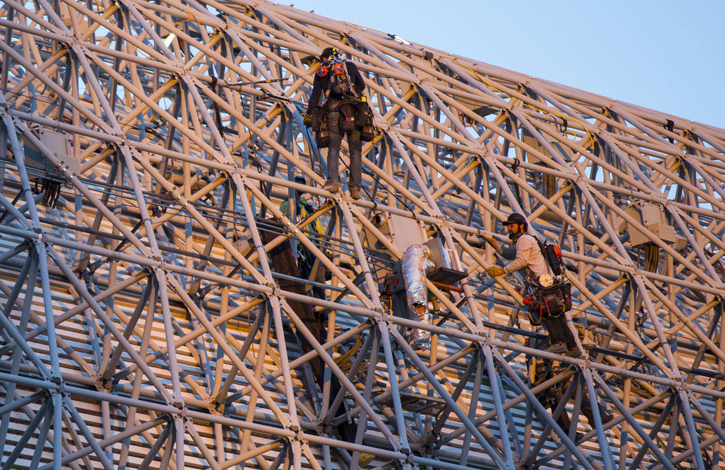 Construction workers work around the exterior of the canopy during the second day of renovation ...
