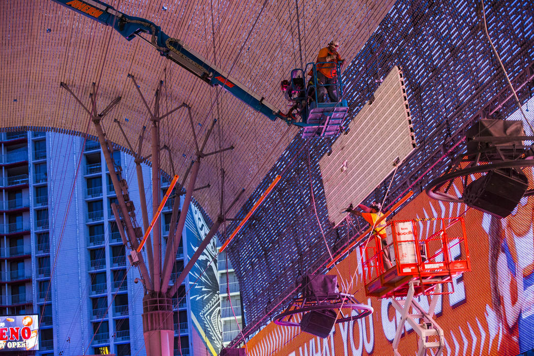 Construction workers lower an old panel during the second day of renovations of the Viva Vision ...
