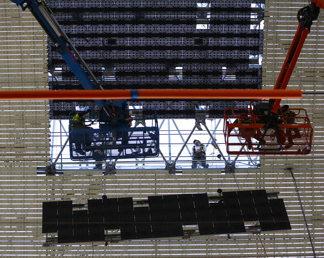 Construction workers install a new panel during the second day of renovations of the Viva Visio ...