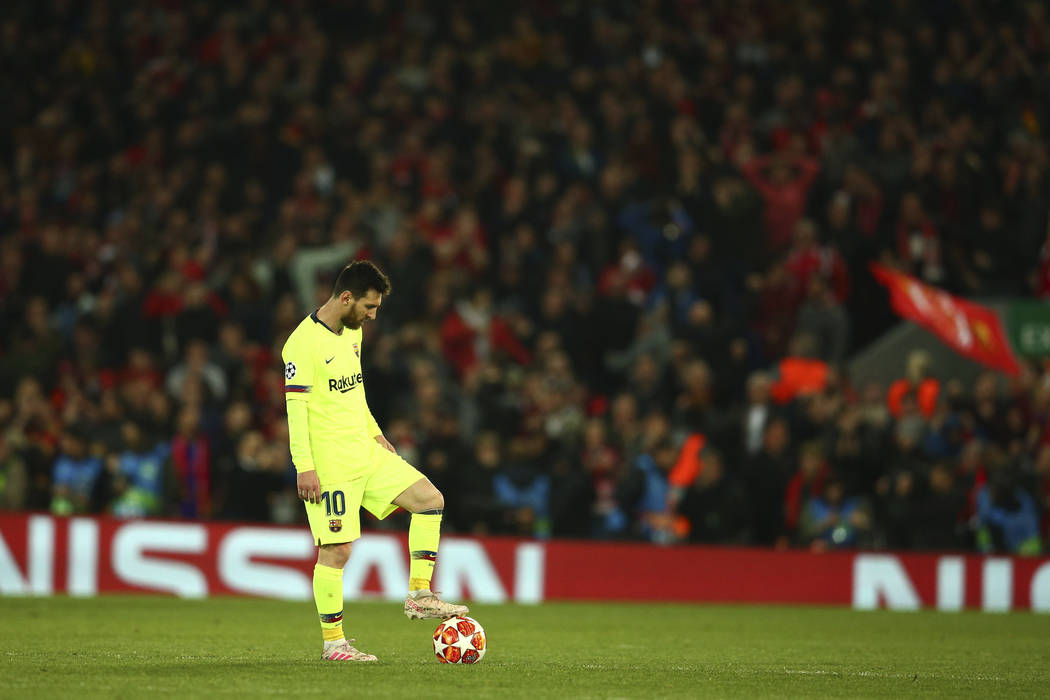 Barcelona's Lionel Messi keeps the ball as Liverpool's Divock Origi celebrates scoring his side ...