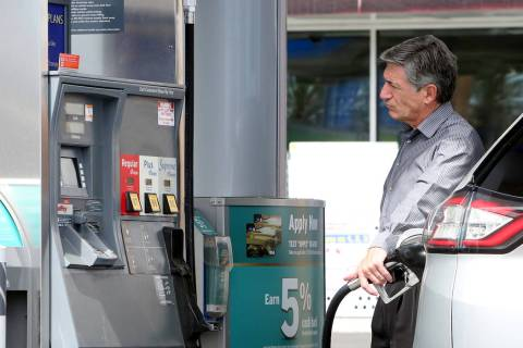 A customer pumps gas at Chevron gas station at the intersection of Tropical Avenue and Fort Apa ...