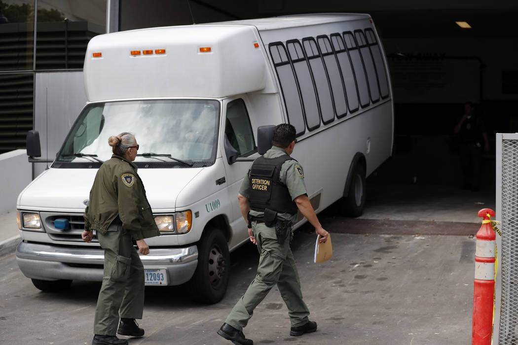 A van carrying asylum seekers from the border is escorted by security personnel as it arrives M ...
