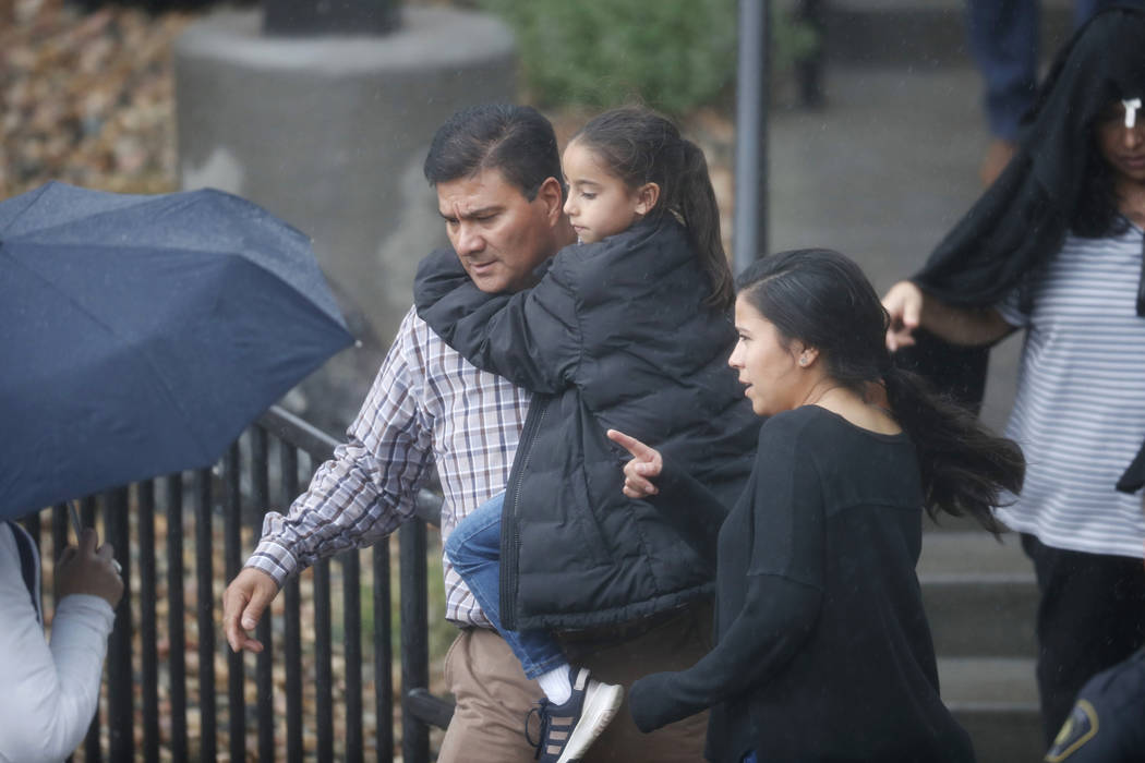 Parents leave a recreation center with their child where students were reunited with their pare ...