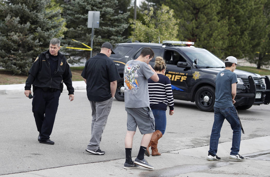 A Douglas County, Colo., Sheriff's Department deputy directs people back to their vehicles park ...