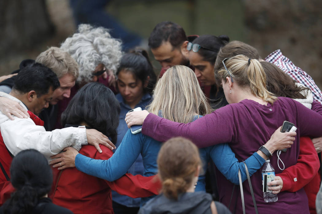 Parents gather in a circle to pray at a recreation center where students were reunited with the ...