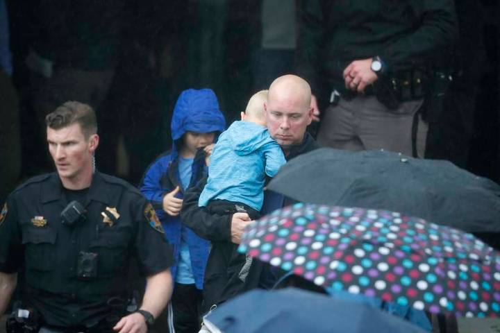 A parent leaves the recreation center where students were reunited with their parents after a s ...