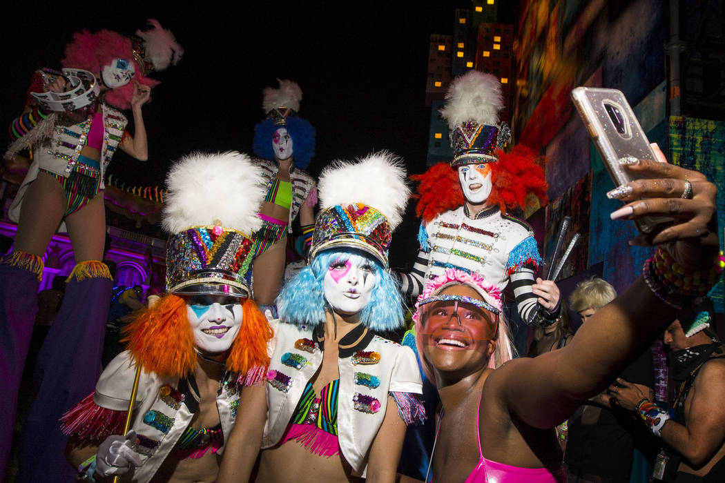 Liz Wright, of Chicago, records with her phone while posig with a group of costumed perfomers d ...