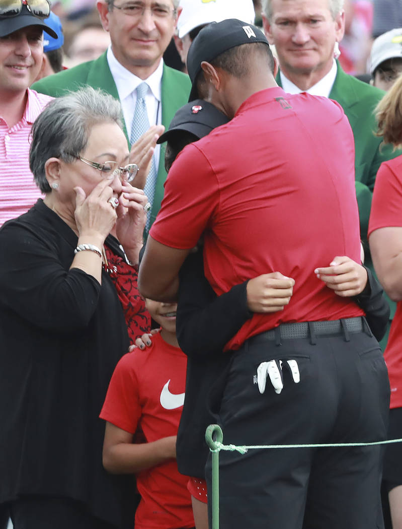 Tiger Woods' mother Kultida Woods wipes away tears as he hugs his daughter Sam and son Charlie ...