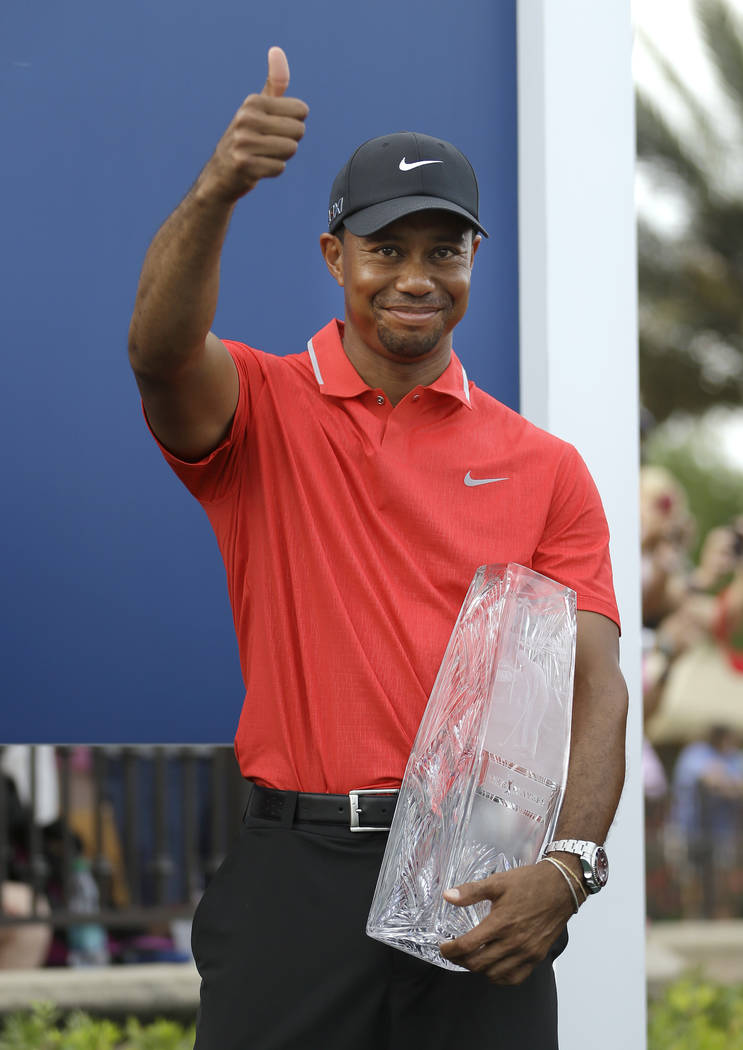FILE - In this May 12, 2013, file photo, Tiger Woods gives a thumbs-up as he holds the trophy a ...