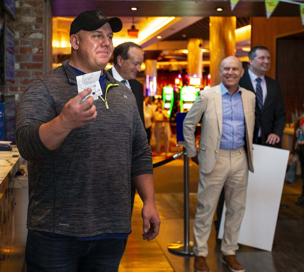 James Adducci of Wisconsin shows off his $1,190,000 winning payout tickets from the William Hil ...