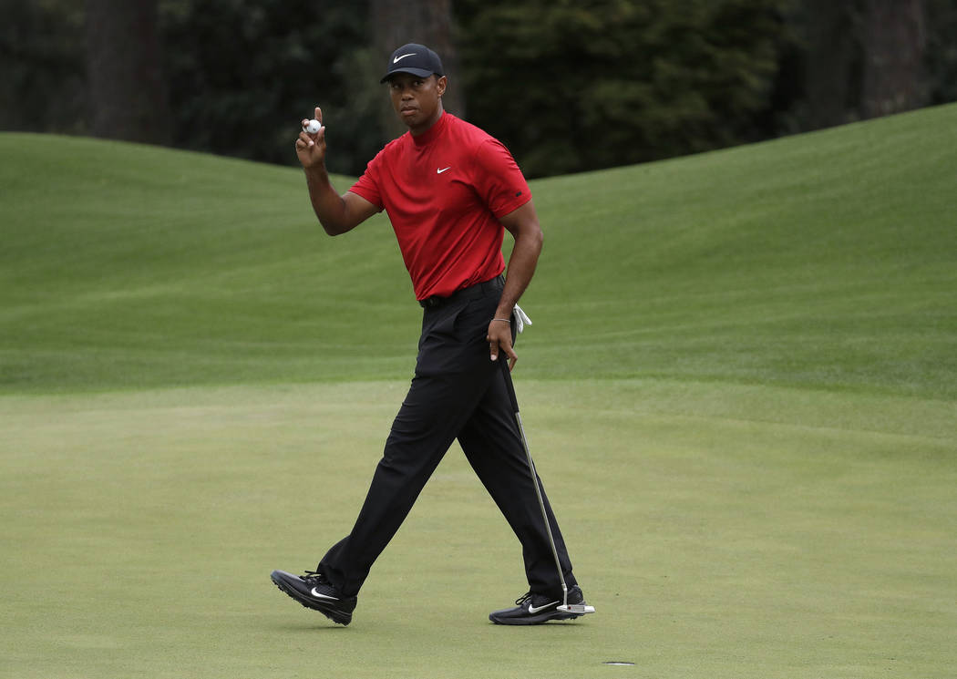 FILE - In this April 14, 2019, file photo, Tiger Woods waves on the eighth hole during the fina ...