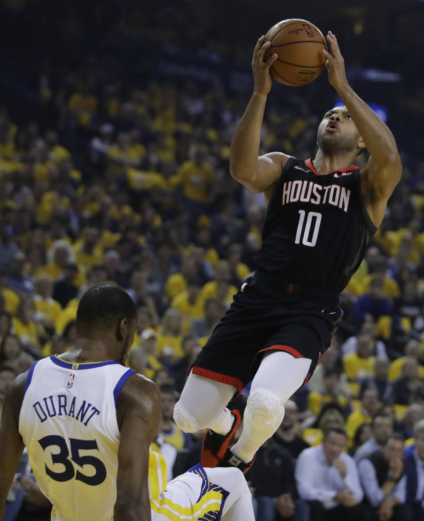 Houston Rockets' Eric Gordon, right, shoots over Golden State Warriors' Kevin Durant (35) durin ...