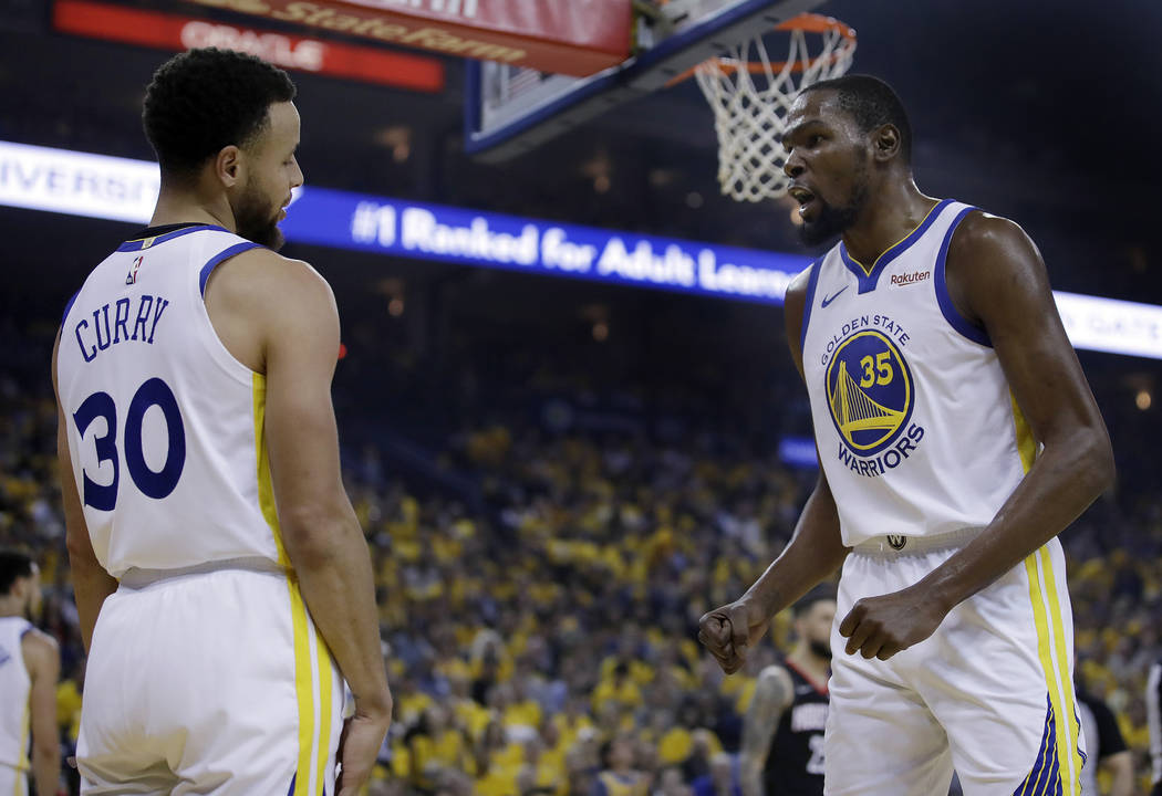 Golden State Warriors' Kevin Durant, right, speaks with Stephen Curry (30) after Curry was call ...