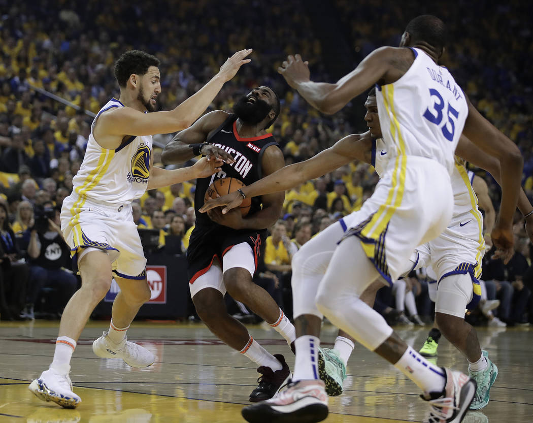 Houston Rockets' James Harden, second from left, drives the ball against Golden State Warriors' ...