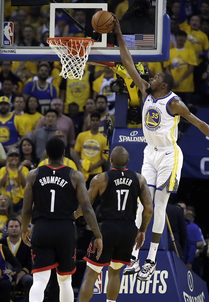 Golden State Warriors' Kevin Durant, right, scores over Houston Rockets' PJ Tucker (17) and Ima ...