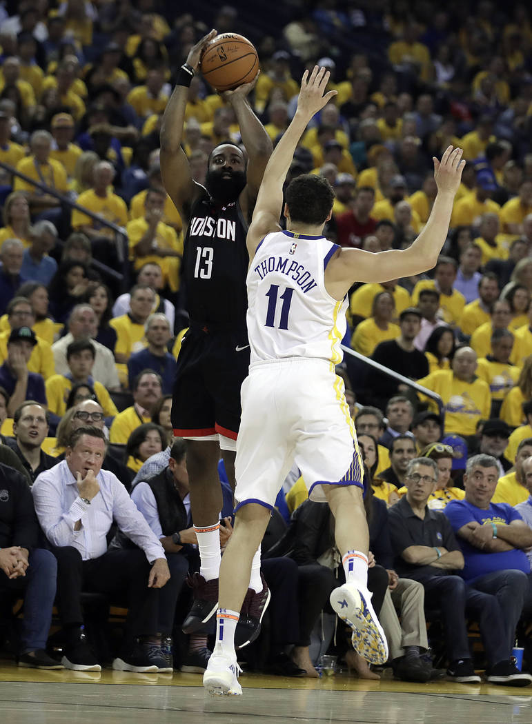 Houston Rockets' James Harden, left, shoots against Golden State Warriors' Klay Thompson (11) d ...