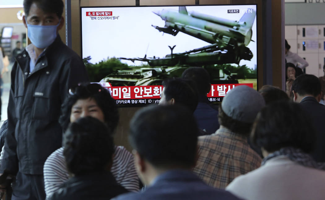 People watch a TV showing file footage of North Korea's missile during a news program at the Se ...