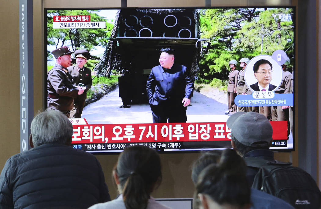 People watch a TV showing a file photo of North Korean leader Kim Jong Un, top center, during a ...