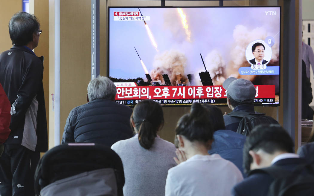 People watch a TV showing a file photo of North Korea's weapon systems during a news program at ...