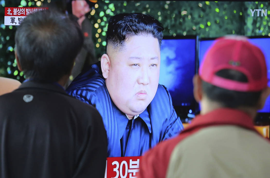 People watch a TV showing a file photo of North Korean leader Kim Jong Un during a news program ...