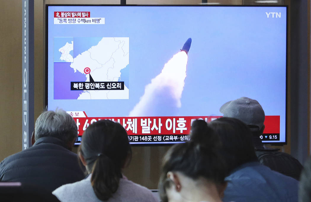 People watch a TV showing file footage of North Korea's missile launch during a news program at ...