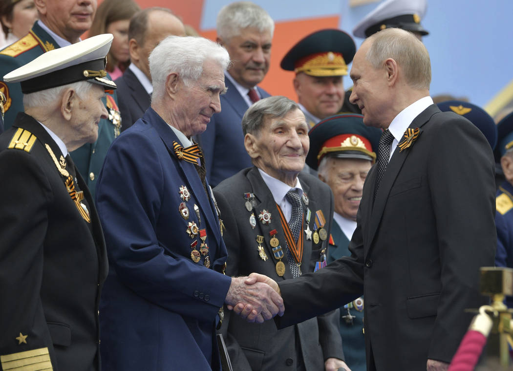 Russian President Vladimir Putin shakes hands with WWII veterans prior to a military parade mar ...