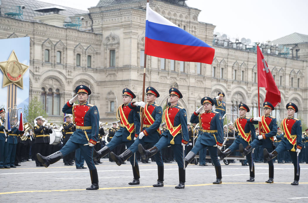 Russian honour guard carry a national flag, left, and a replica of the Victory banner during th ...