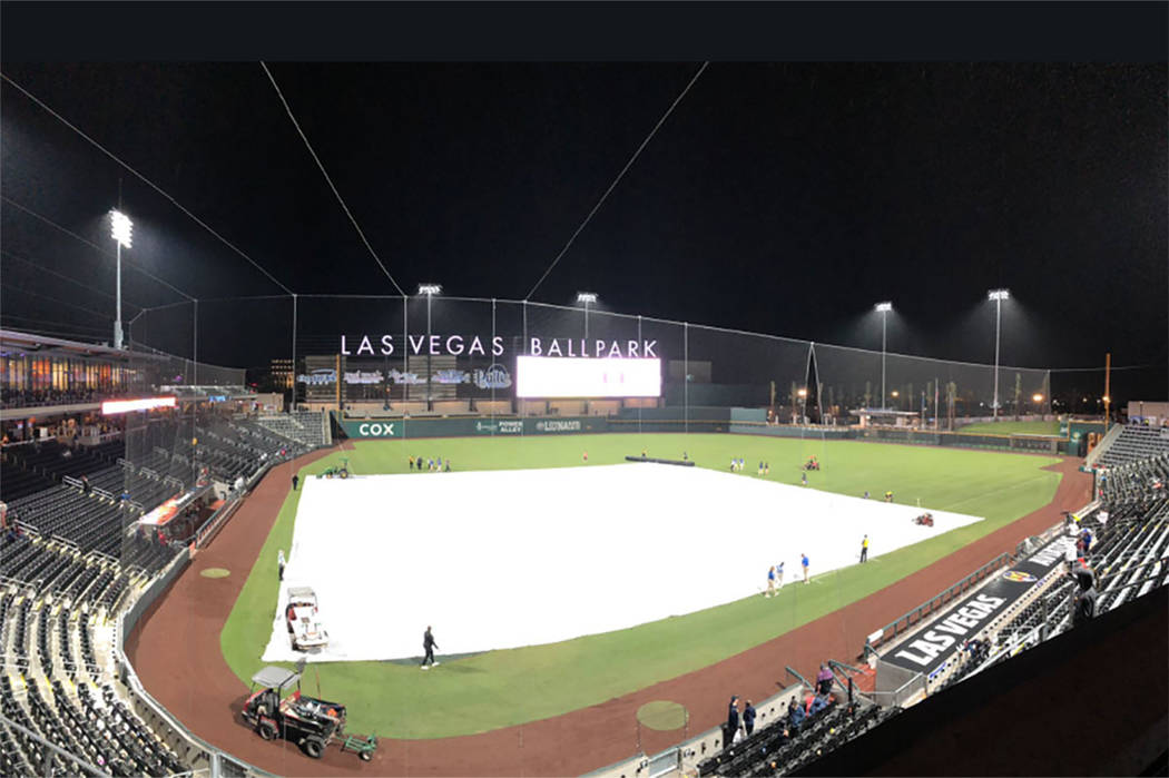 Crews cover the field during a rain delay at Las Vegas Ballpark during a Las Vegas Aviators gam ...