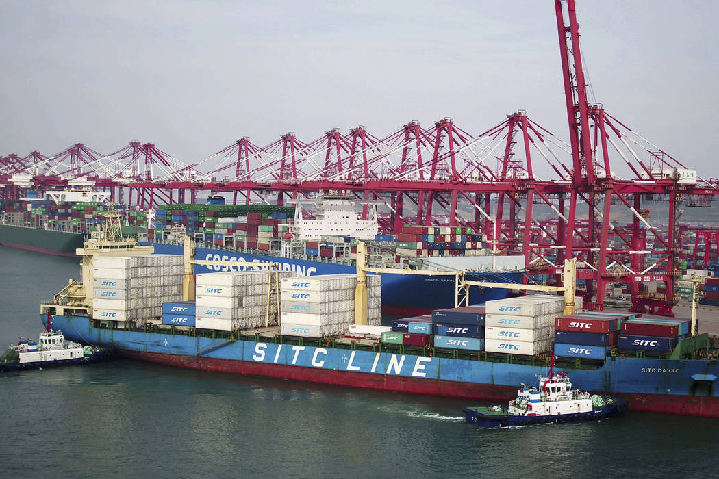 Two barges push a container ship to the dockyard in Qingdao in eastern China's Shandong provinc ...