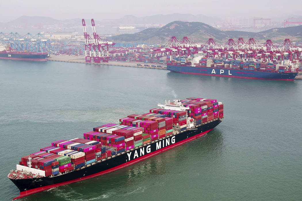 A container ship sails off the dockyard in Qingdao in eastern China's Shandong province Wednesd ...
