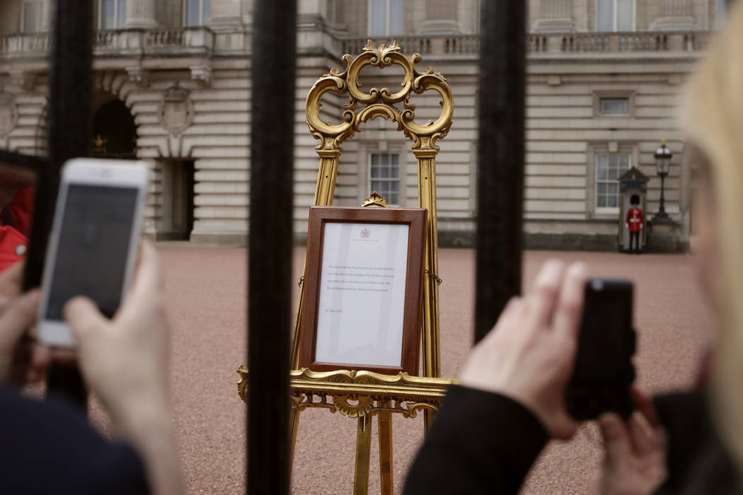 People take pictures of the notice on an easel in the forecourt of Buckingham Palace, London, T ...