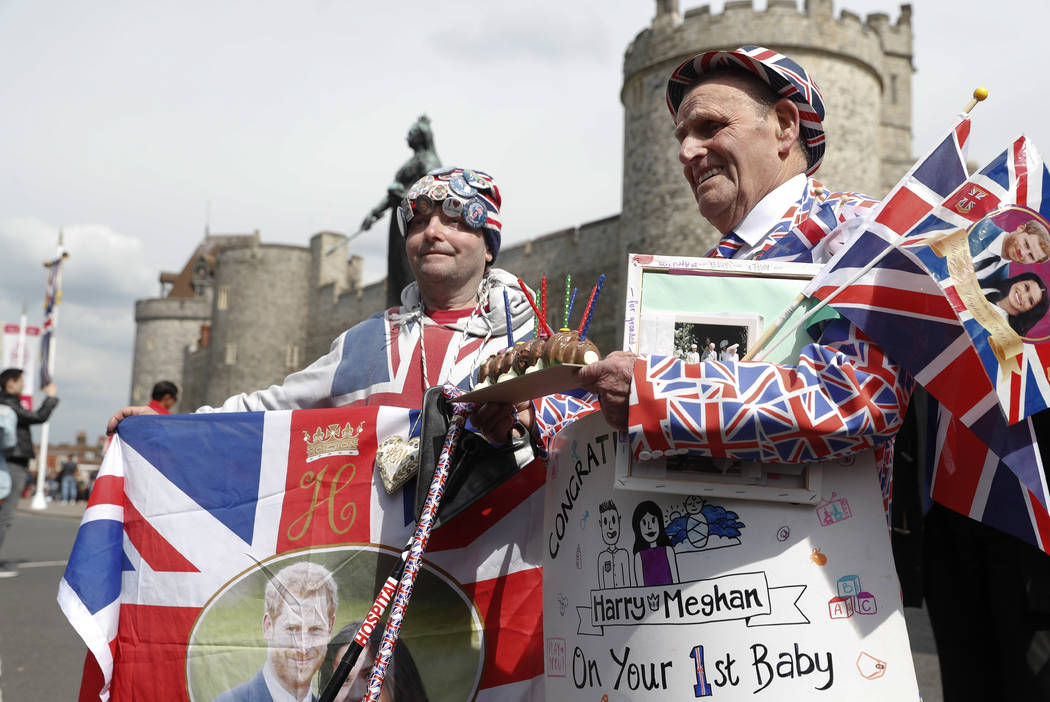 Royal fans John Loughery, left and Terry Hutt pose with flags and banners, outside Windsor Cast ...
