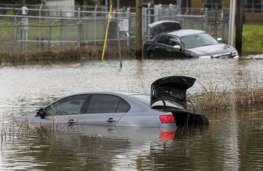 Two vehicles remain stuck in flooded Adams Street following an overnight storm Wednesday, May 8 ...