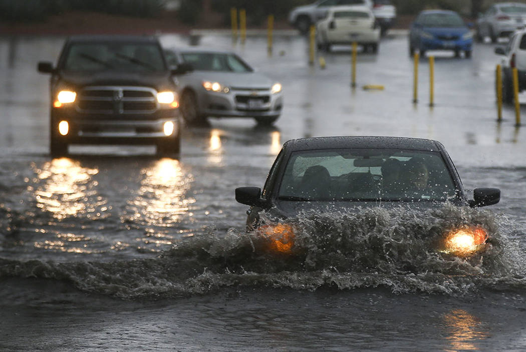 People navigate a flooded parking lot at UNLV in Las Vegas on Saturday, Feb. 18, 2017. (Chase S ...