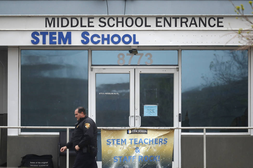 A Douglas County, Colo., Sheriffs Department deputy walks past the doors to the STEM Highlands ...