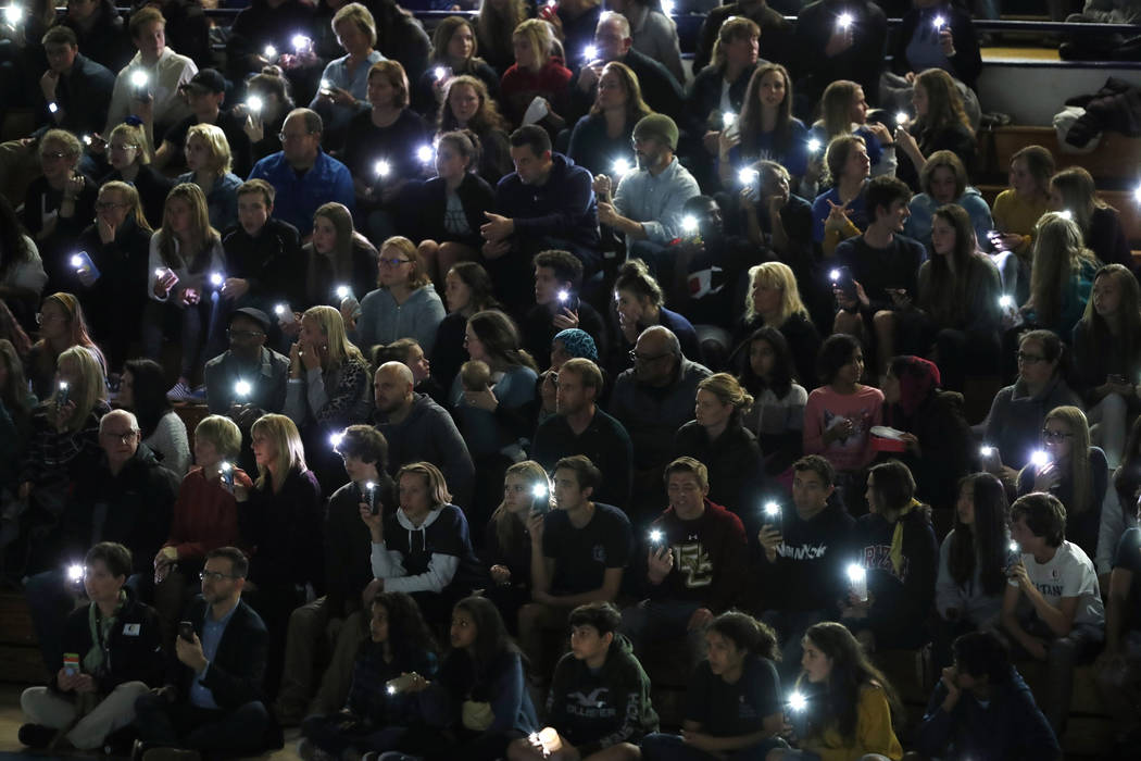 Attendees illuminate their mobile telephones during a community vigil to honor the victims and ...
