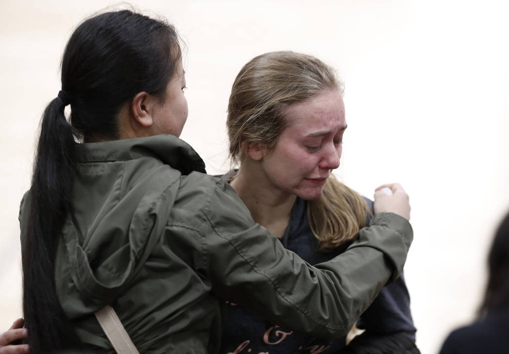 Young women console each other during a community vigil to honor the victims and survivors of y ...