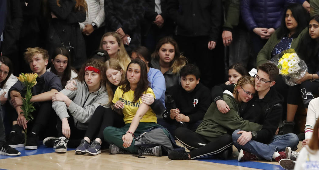 Young people console each other during a community vigil to honor the victims and survivors of ...