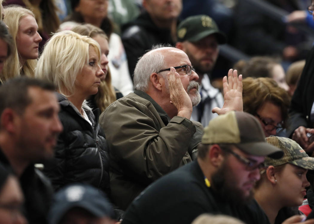 Colorado State Rep. Tom Sullivan, D-Aurora, center, applauds for speakers during a community vi ...
