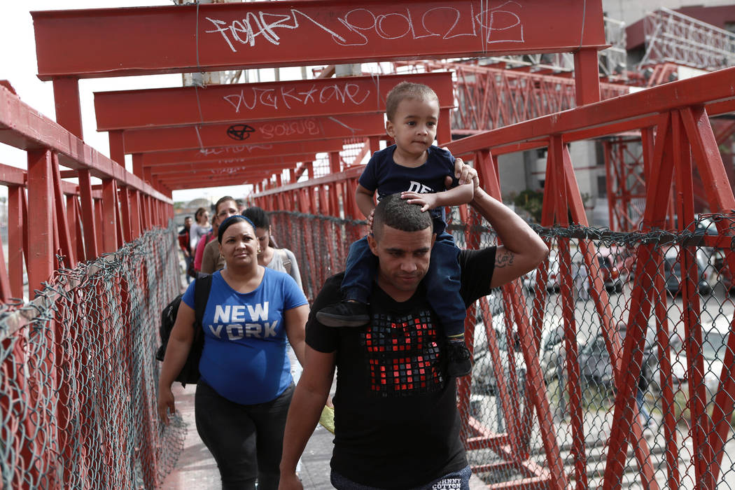 Cuban migrants are escorted in Ciudad Juarez, Mexico, by Mexican immigration officials as they ...