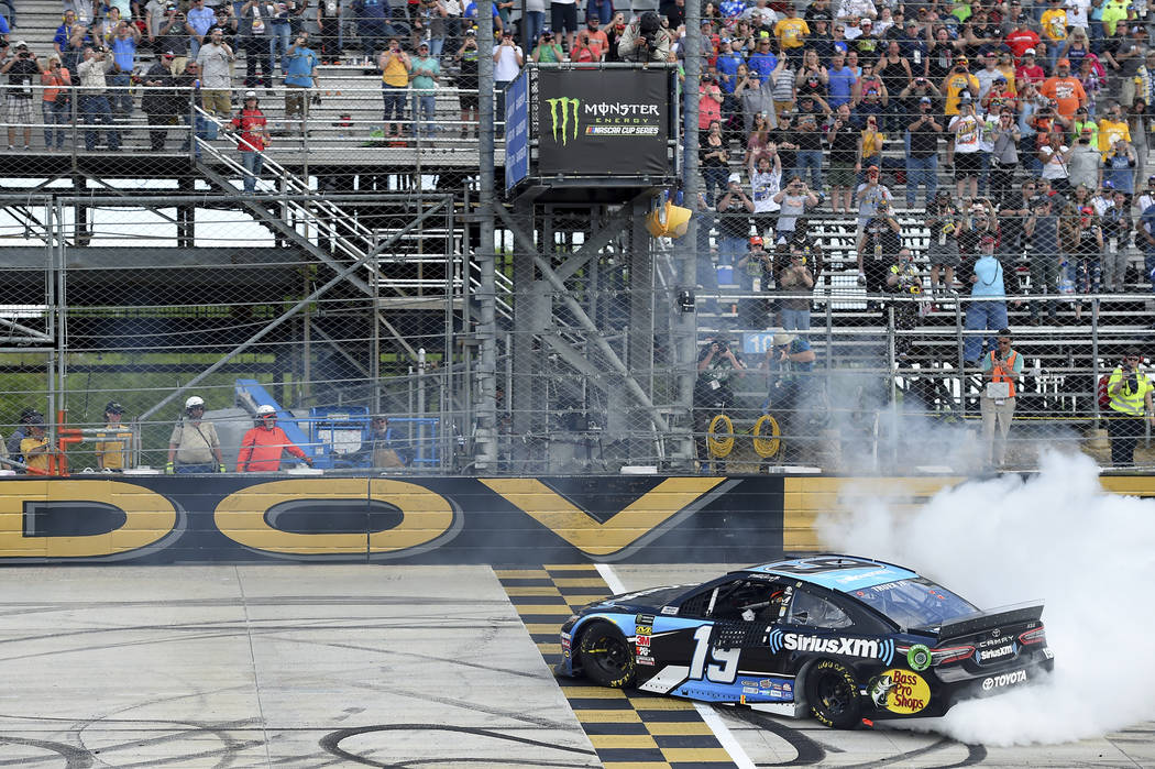 Driver Martin Truex Jr. (19) performs a burnout after winning the NASCAR Cup Series auto race, ...