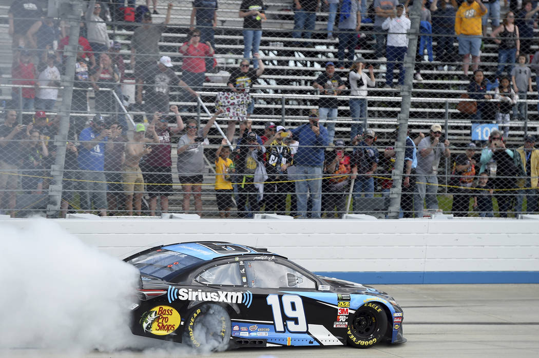 Driver Martin Truex Jr. (19) performs a burnout after winning a NASCAR Cup Series auto race, Mo ...
