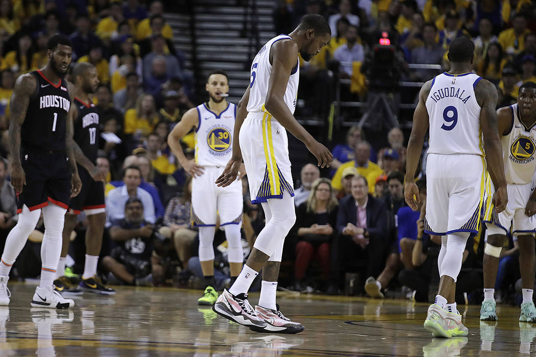 Golden State Warriors' Kevin Durant, center, limps off the court during the second half of Game ...