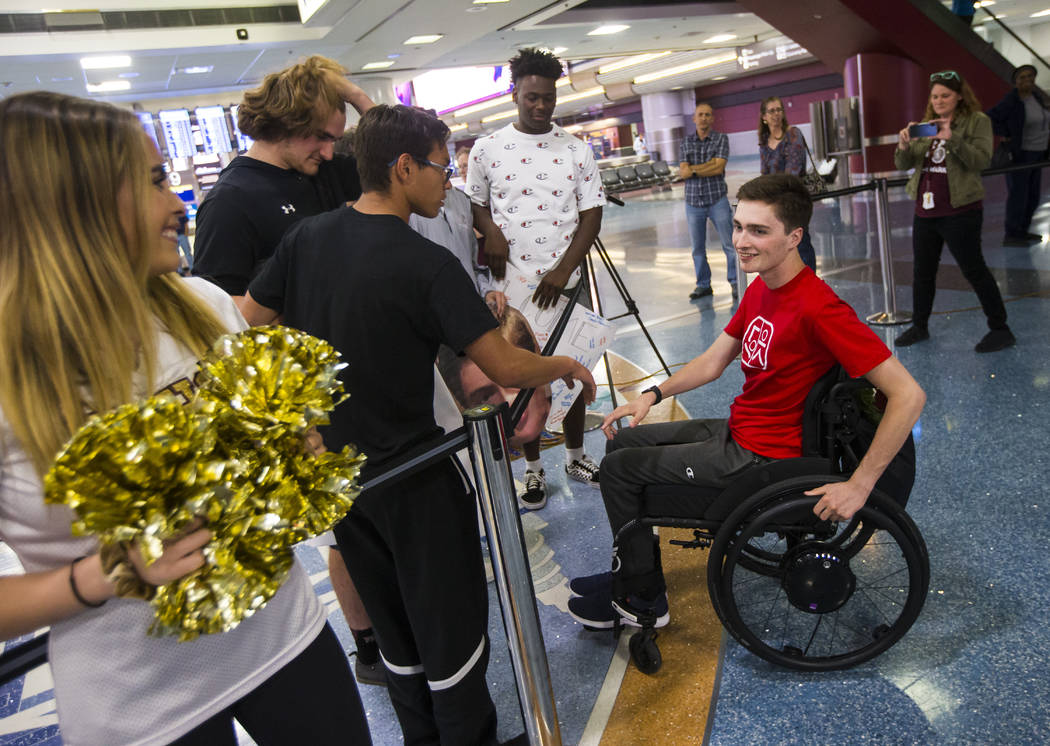 Faith Lutheran senior Mark Wilbourne, in red, greets friends at McCarran International Airport ...