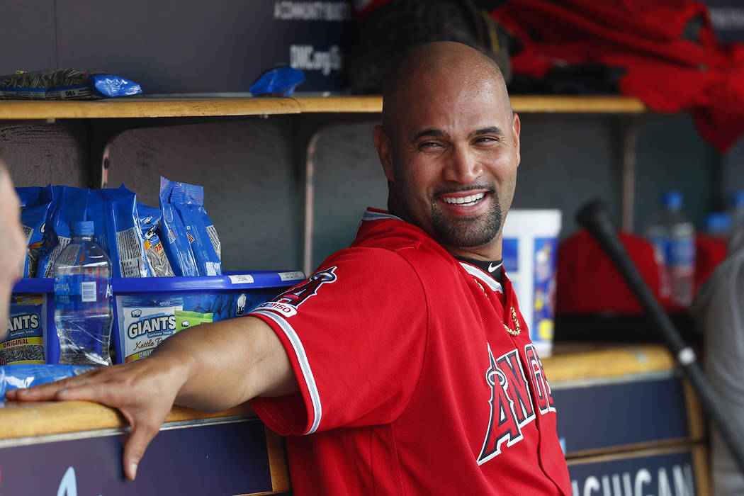 Los Angeles Angels' Albert Pujols smiles in the dugout after hitting a solo home run in the thi ...