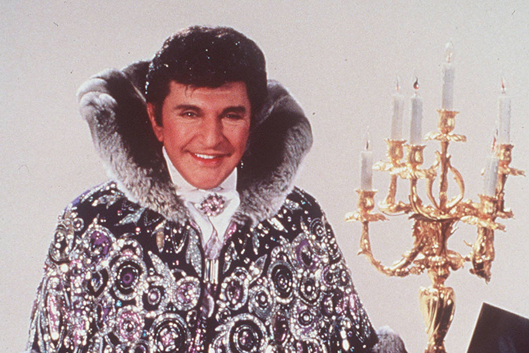 Liberace, wearing his shiny rings and dress, is shown 1987. (AP Photo)