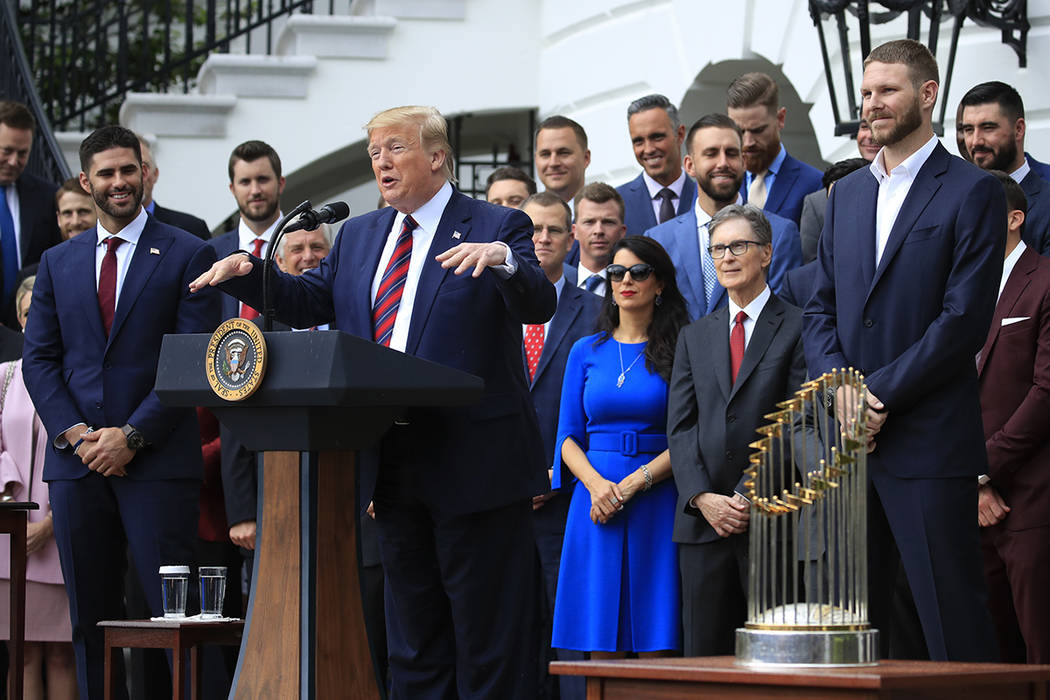 President Donald Trump flanked by Red Sox players Chris Sale, right, and J. D. Martinez, left, ...