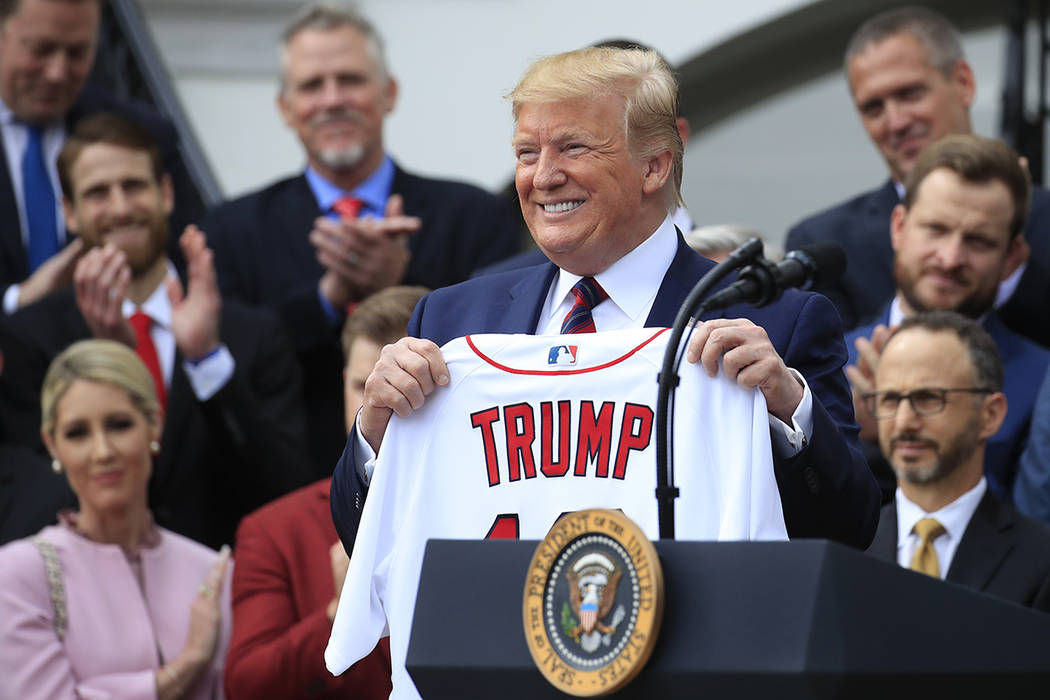 President Donald Trump shows off a Red Sox jersey presented to him during a ceremony welcoming ...